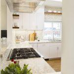 Interior Designer Redondo Beach modern coastal kitchen with white cabinets, marble countertops and gas cook top. Manhattan Beach modern coastal home.