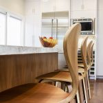 Redondo Beach modern coastal wood kitchen island counter stools with wall oven and cabinetry beyond. Manhattan Beach modern coastal home.