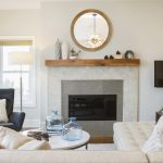 Modern Coastal Redondo Beach living room fireplace design white plaster and wooden mantle with decorative mirror above and side chair. Manhattan Beach modern coastal home