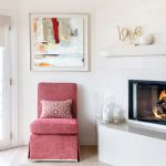 Bright and beachy living room with whitewashed corner fireplace with red upholstered side chair in Manhattan Beach