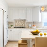 Beachy contemporary kitchen with white cabinets and neutral upholstered stools in Manhattan Beach