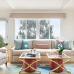 Beachy contemporary living room with red upholstered ottomans and gold side tables in Manhattan Beach