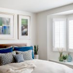 Bright and beachy master bedroom with blue accent pillows, artwork and accessories in Manhattan Beach